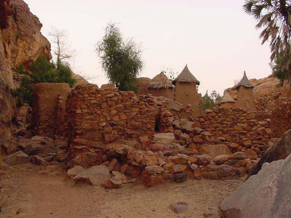 Dogon huts behind a stone wall