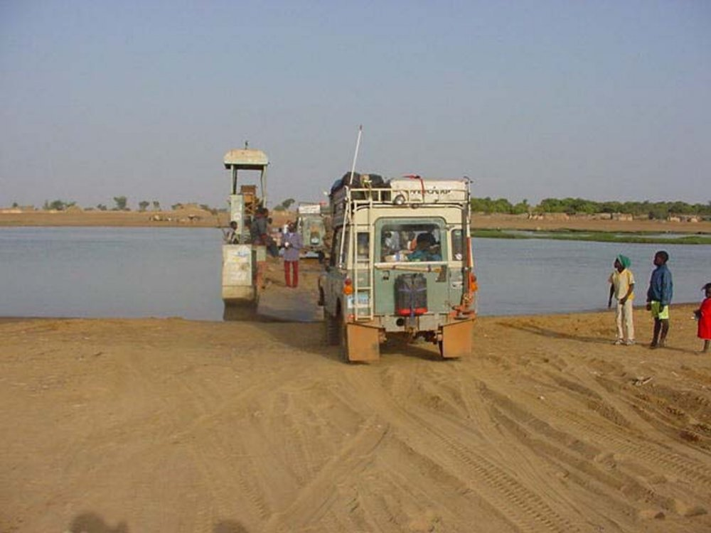 Our expedition trucks boarding the ferry to cross the Bani River