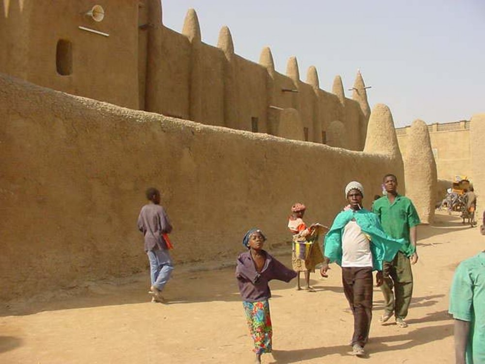 Locals pass by the mud walls
