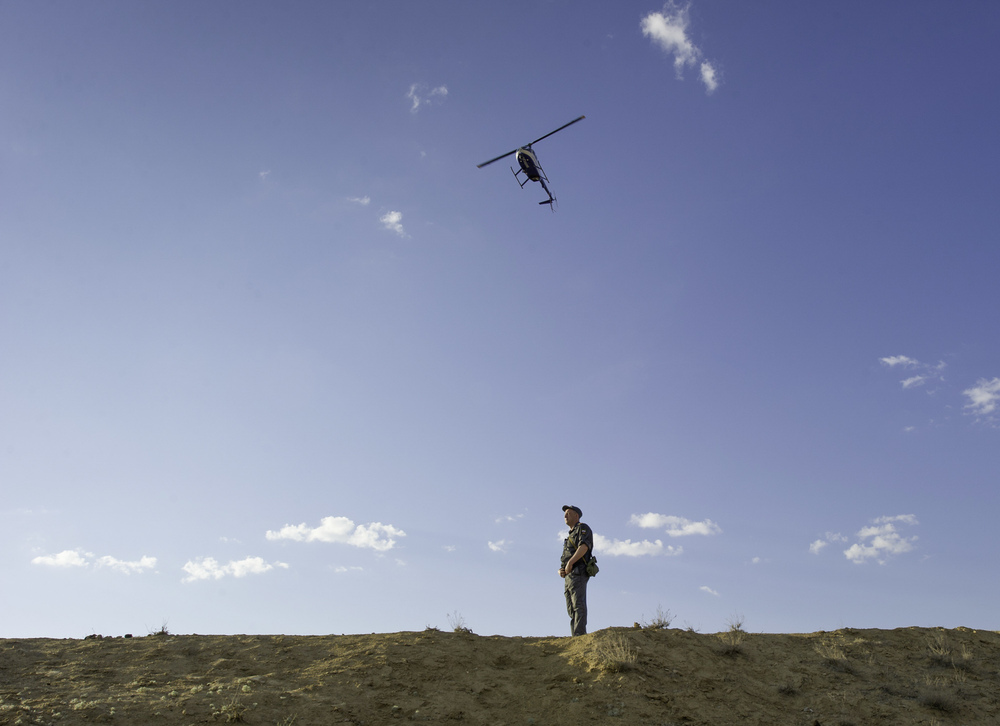 A Russian security guard stands watch as a Russian military helicopter flies overhead during the rollout of the Soyuz TMA-02M rocket to the launch pad at the Baikonur Cosmodrome in Kazakhstan on Sunday, June 5, 2011. (NASA/Carla Cioffi)
