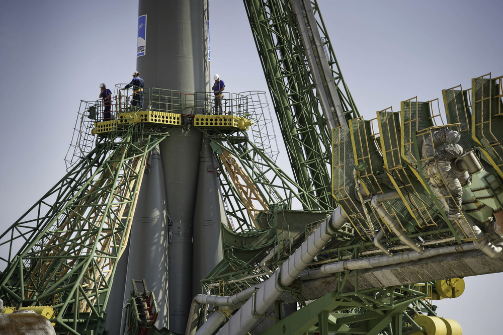 Launch pad engineers at the Baikonur Cosmodrome in Kazakhstan are dwarfed by the large gantry mechanisms at the base of the Soyuz TMA-02M rocket following its rollout to the pad on Sunday, June 5, 2011. The rocket is being prepared for launch June 8 to carry the crew of Expedition 28 to the International Space Station. (NASA/Carla Cioffi)