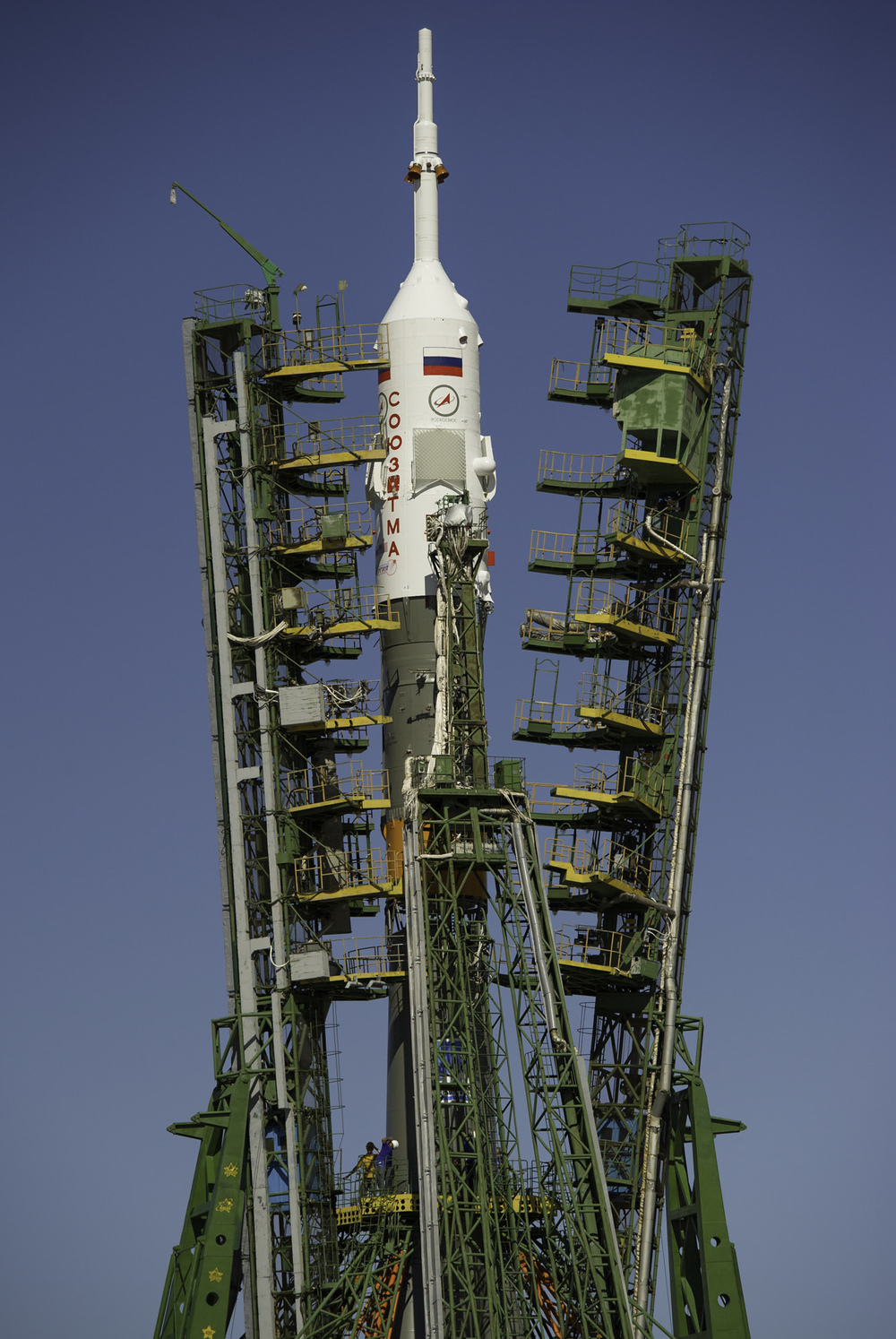Large gantry mechanisms on either side of the Soyuz TMA-205M spacecraft are raised into position to secure the rocket at the launch pad on Thursday, July 12, 2012 at the Baikonur Cosmodrome in Kazakhstan. (NASA/Carla Cioffi)