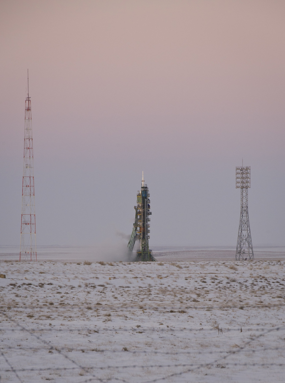 The Soyuz TMA-03M spacecraft is seen at dusk an hour before launch at the Baikonur Cosmodrome in Kazakhstan, Wednesday, Dec. 21, 2011. The crew of Expedition 30, NASA Flight Engineer Don Pettit, Soyuz Commander Oleg Konenko, ESA (European Space Agency) Andre Kuipers launched at 7:16pm local time to the International Space Station. (NASA/Carla Cioffi)