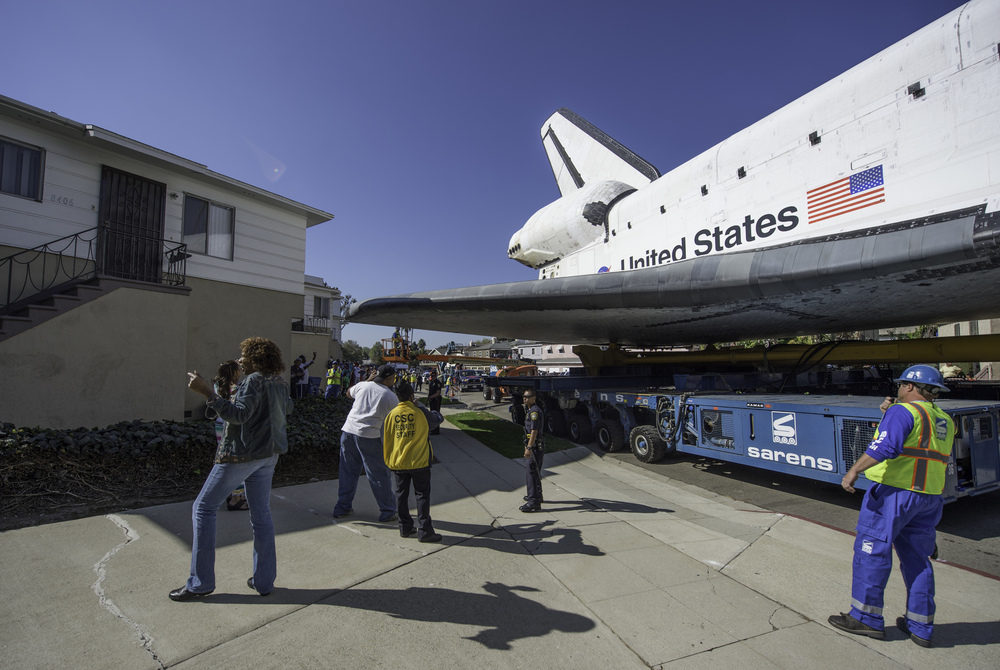 Space shuttle Endeavour is seen on the streets of Inglewood, CA as it narrowly passes a house on Saturday, Oct. 13, 2012. Endeavour, built as a replacement for space shuttle Challenger, completed 25 missions, spent 299 days in orbit, and orbited Earth 4,671 times while traveling 122,883,151 miles. Beginning Oct. 30, the shuttle will be on display in the CSC's Samuel Oschin Space Shuttle Endeavour Display Pavilion, embarking on its new mission to commemorate past achievements in space and educate and inspire future generations of explorers. (NASA/Carla Cioffi)