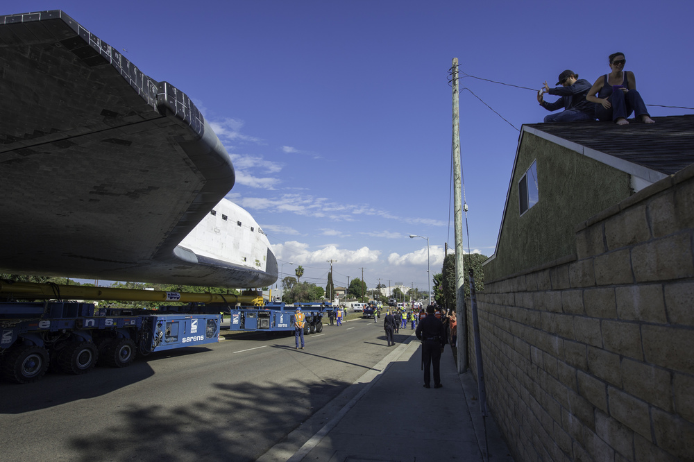 A spectator on the roof of a building photographs space shuttle Endeavour as it passes by on its way to its new home at the California Science Center in Los Angeles, Friday, Oct. 12, 2012. Endeavour, built as a replacement for space shuttle Challenger, completed 25 missions, spent 299 days in orbit, and orbited Earth 4,671 times while traveling 122,883,151 miles. Beginning Oct. 30, the shuttle will be on display in the CSC's Samuel Oschin Space Shuttle Endeavour Display Pavilion, embarking on its new mission to commemorate past achievements in space and educate and inspire future generations of explorers. (NASA/Carla Cioffi)