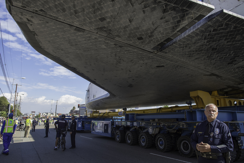 A policeman stands guard as space shuttle Endeavour passes by on its way to its new home at the California Science Center in Los Angeles, Friday, Oct. 12, 2012. Endeavour, built as a replacement for space shuttle Challenger, completed 25 missions, spent 299 days in orbit, and orbited Earth 4,671 times while traveling 122,883,151 miles. Beginning Oct. 30, the shuttle will be on display in the CSC's Samuel Oschin Space Shuttle Endeavour Display Pavilion, embarking on its new mission to commemorate past achievements in space and educate and inspire future generations of explorers. (NASA/Carla Cioffi)