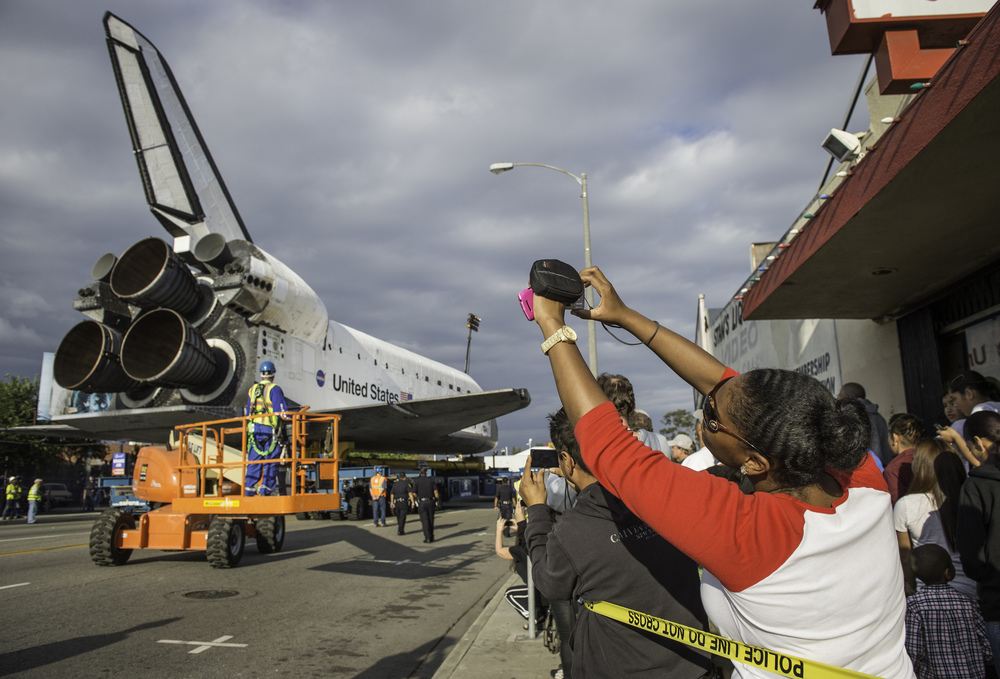 Spectators are seen photographing space shuttle Endeavour as it passes by on its way to its new home at the California Science Center, Friday, Oct. 12, 2012, in Inglewood. Endeavour, built as a replacement for space shuttle Challenger, completed 25 missions, spent 299 days in orbit, and orbited Earth 4,671 times while traveling 122,883,151 miles. Beginning Oct. 30, the shuttle will be on display in the CSC's Samuel Oschin Space Shuttle Endeavour Display Pavilion, embarking on its new mission to commemorate past achievements in space and educate and inspire future generations of explorers. (NASA/Carla Cioffi)