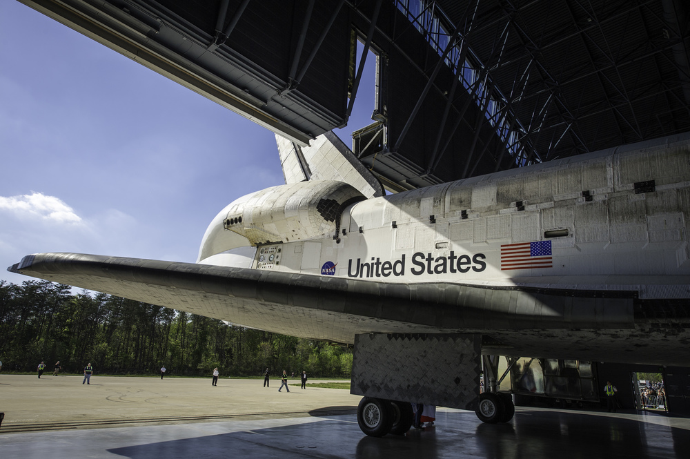 Space shuttle Discovery is rolled into its hangar at the Steven F. Udvar-Hazy Center Thursday, April 19, 2012 in Chantilly, Va. Discovery will be permanently housed at the Udvar-Hazy Center, part of the Smithsonian Institution's Air and Space Museum. Discovery, the first orbiter retired from NASA's shuttle fleet, completed 39 missions, spent 365 days in space, orbited the Earth 5,830 times, and traveled 148,221,675 miles. NASA will transfer Discovery to the National Air and Space Museum to begin its new mission to commemorate past achievements in space and to educate and inspire future generations of explorers. (NASA/Carla Cioffi)