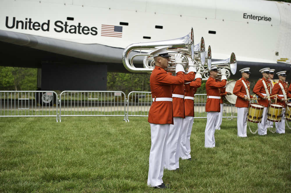 Space shuttle Enterprise is seen with the United States Marine Corp Drum and Bugle Corps and Color Guard at the Steven F. Udvar-Hazy Center Thursday, April 19, 2012 in Chantilly, Va. Enterprise was the first space shuttle orbiter, built for NASA to perform test flights in the atmosphere and was not capable of spaceflight. It has been on display at the Udvar-Hazy Center's Space Hangar since 2004. Enterprise will be transferred to the Intrepid Sea, Air and Space Museum in New York City. (NASA/Carla Cioffi)