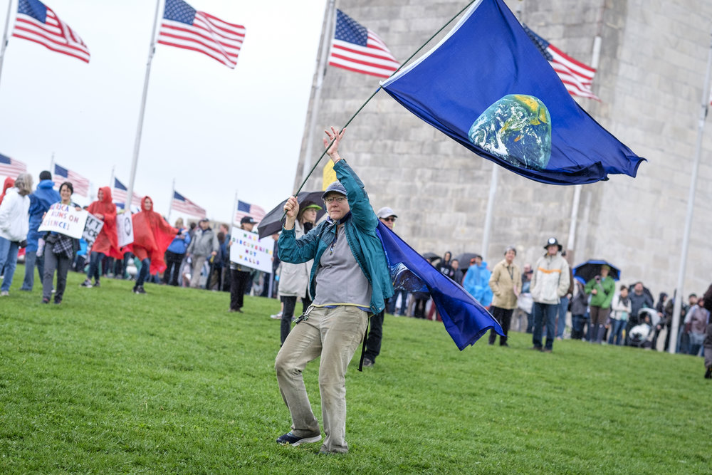 "Sue Kozel, a nurse from Annapolis, MD, flies the Earth Day flag at the March for Science on the National Mall on Earth Day, Saturday, April 22, 2017 in Washington, DC. When asked why she attended the march her response was ""I'm here for the planet, just for the planet. We gotta take care of her, that's for sure. I too am an athlete for the earth, a cheerleader. You have to take care of her.""  Thousands gathered in the nation's capital as scientists and science supporters across the world participate in the first-ever global march for science. More than 600 locations world-wide participated in this event."