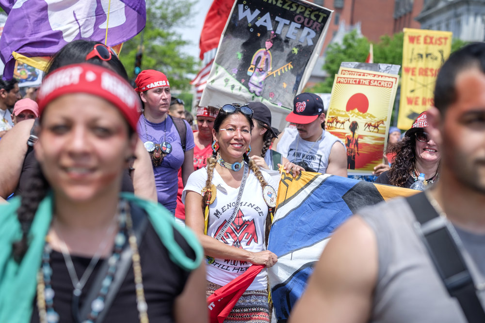 "Marla Mahkimetas, center, a member of the Menominee Indian Tribe of Wisconsin, is seen marching in the Protectors of Justice contingency at the Peoples Climate March in Washington, DC on Saturday, April 29, 2017. She and her people are fighting the Back 40 proposed open pit mine on the border of Wisconsin and Upper Michigan. ""We are here to teach non-indigenous people about the connection to our earth and water,"" she said. ""And with that connection, if you know that connection, as indigenous people that is our innate knowing, and our innate responsibility to teach that. People with that connection will no longer destroy the earth or the water."" The Peoples Climate March took place on the 100th day of Donald Trump's presidency. Marchers surrounded the White House in a silent sit-in to recognize the damage caused by the Trump administration over the last 100 days."