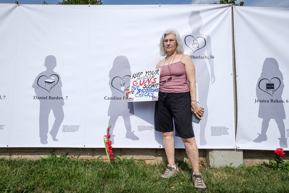 "Karen Bralove, of Bethesda, MD, is seen in front of a long banner illustrating the victims of the Sandy Hook Elementary School mass shooting at the Women's March From #NRA2DOJ rally in front of the National Rifle Association Headquarters in Fairfax, VA on Friday, July 14, 2017. I have seen Karen, who is normally seen with her bull horn, at all of the events I have photographed since starting this project. This is the first time I had a chance to chat with her. The following is what she had to say on why she was at this event: ""It is such a profoundly deep place for me. I am so enraged at the lack of decency. I am so enraged at the man and people in the White House. And now especially we're here because of lax gun laws. And it is insane and makes no sense. I come with my bull horn because literally can't help myself. I am just kind of driven to exercising my right to say this is not right. The Brady Bill should have been passed decades ago. Ninety-one people a day are killed with a gun. Dear gun owners we're not trying to confiscate your guns, even though Donny said that in the campaign. He said, 'they are trying to take away your guns.' Sorry, we're not doing that. We just want to register people. And just wondering why you think you need machine guns, AKs whatever they are, not sure why we need that for hunting and practicing. So that's my story. I am enraged very deep down inside of me."""