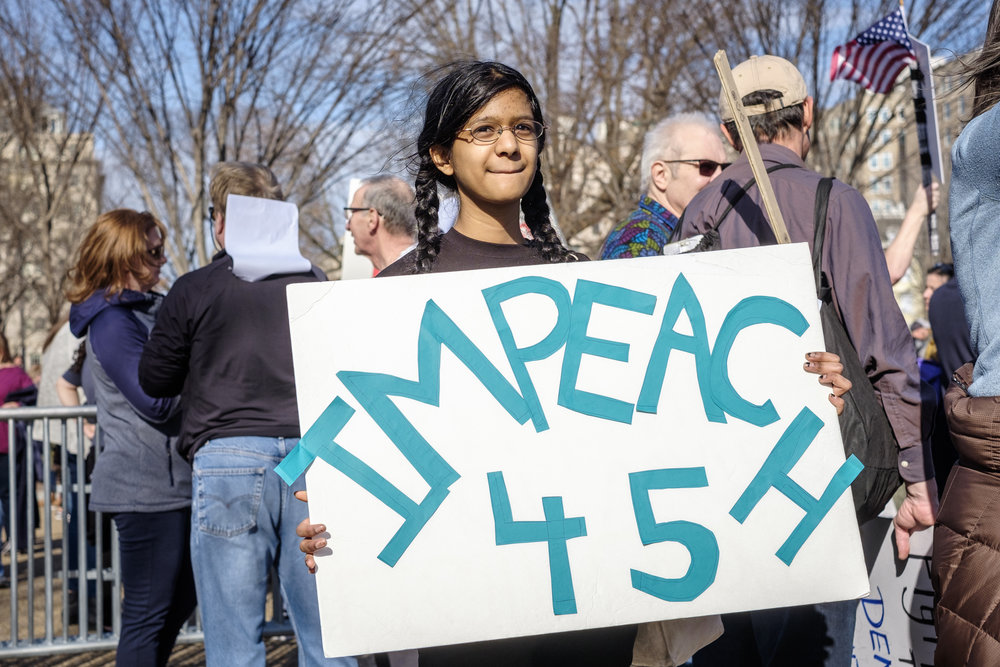 "Khiyali K.P., a 14 year old high school student from Bel Air, MD is seen at the Muslim/Refugee Ban: A Year of Resistance rally on Saturday, January 27, 2018 in Washington, DC. She joined others in protest and said, ""Well if the president does things that he is not supposed to and that warrant impeachment we clearly have to impeach him. So I am here to encourage that."" Hundreds gathered at the White House to stand in solidarity and protest the one-year anniversary of the first Muslim and Refugee Ban by the Trump administration."