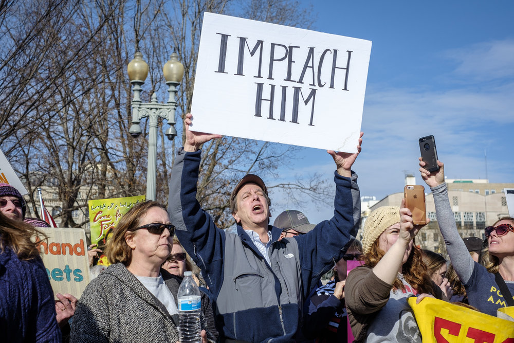 "Mark Vosburgh from North Potomac, MD is seen at the Muslim/Refugee Ban: A Year of Resistance rally on Saturday, January 27, 2018 in Washington, DC. He joined others at the rally and said, ""I'm here because I'm protesting the President of the United States. His mysoginistic, impulsive, spiteful, zenophobic, racist, scheming presidency. And I'm urging for an impeachment.""Hundreds gathered at the White House to stand in solidarity and protest the one-year anniversary of the first Muslim and Refugee Ban by the Trump administration."