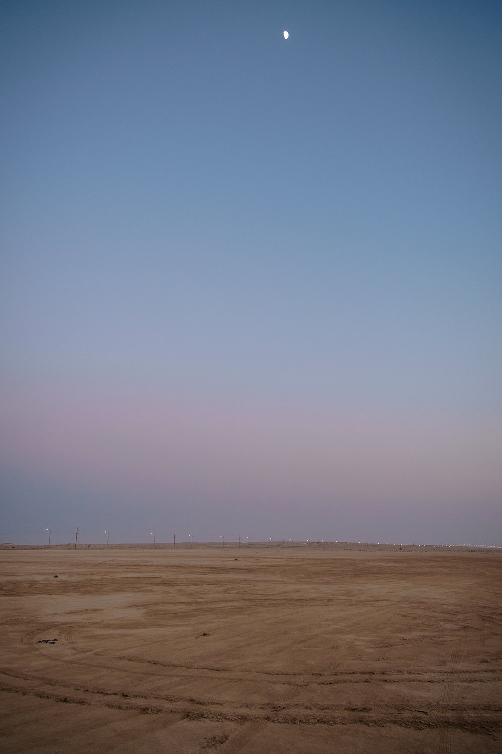 The moon is seen rising above the desert in Zekreet at dusk.
