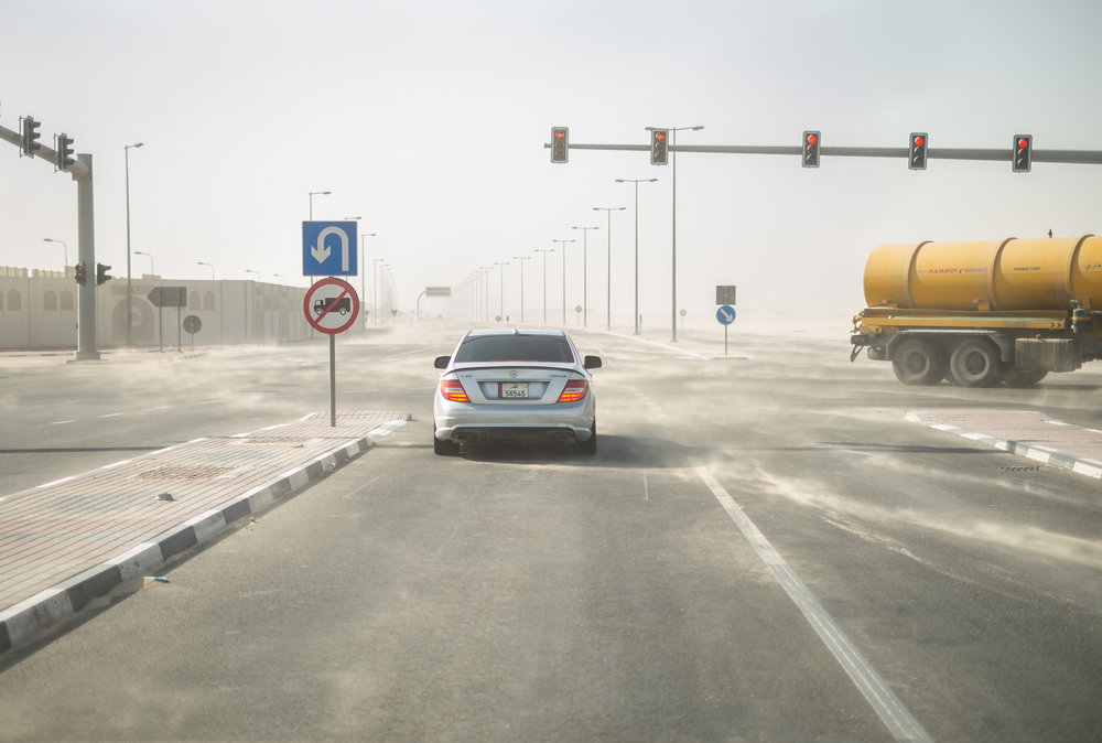 A mercedes and a sewage truck are seen in a dust storm on the northern edge of Doha.