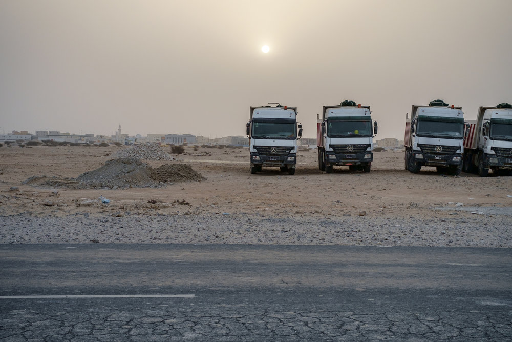 Dumpster trucks are lined up on their day off as the sun sets behind them. Desert dust is often in the air creating an other-worldly atmosphere.