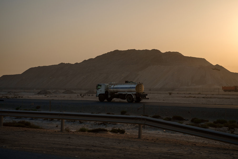 The ubiquitous semi truck, this one carrying water, is seen at sunrise at a massive construction site just north of Lusail City.
