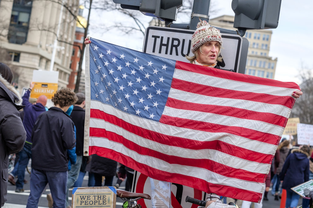 A woman holds a US flag at the first Anti Immigration Ban march on Saturday, January 29, 2017 in Washington, DC. Thousands of people marched from the White House to the U.S. Capitol to protest Trump's executive order banning immigration by refugees and foreign nationals from seven predominantly Muslim countries into the United States.