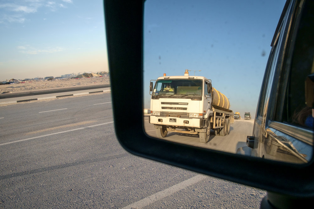The ubiquitous semi truck is seen at the end of the day leaving a massive construction site on the outskirts of Doha.