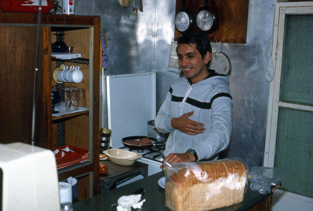 """Pablo Morales förbereder mat i köket. Notera att förläggning, """"kontoret"""", köket och matsal, allt låg i ett öppet rum."""