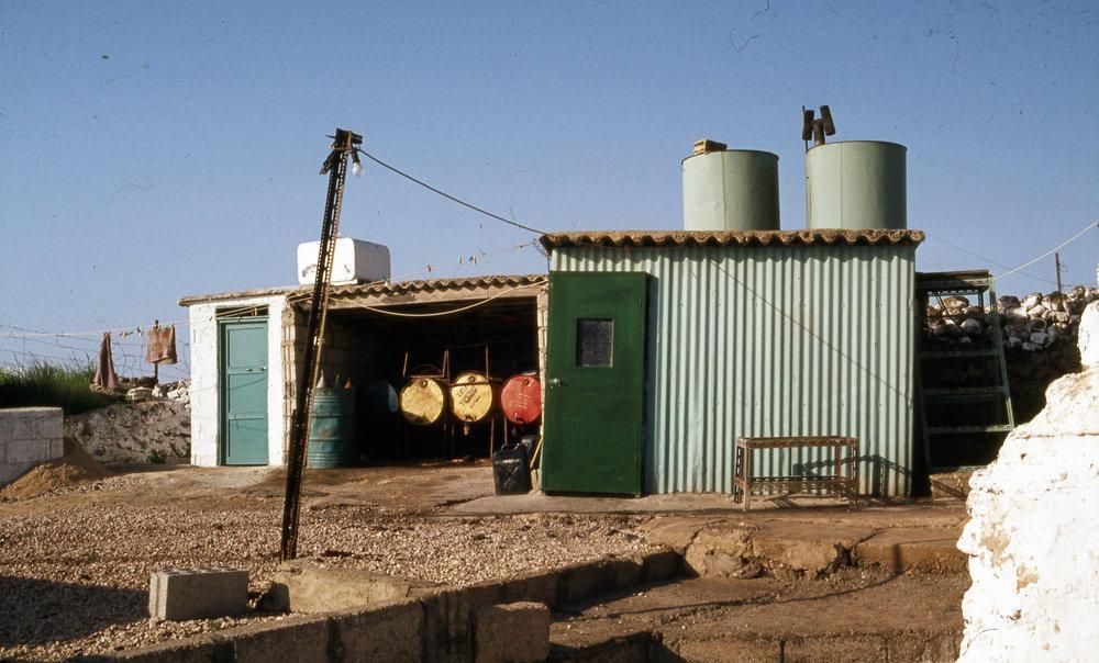 """OP-n omgavs av en mur med grind. Invändigt en caravan, ett litet hus. Som kringbyggnad med dieselgenerator, reserv- el generator. Toalett som under min tid 1984 till slut blev vattentoalett. Toaletten till vänster i bild. Över denna dess vattenbehållare. Dusch till höger med vattenbehållare. Bakom ligger """"heatern""""."""