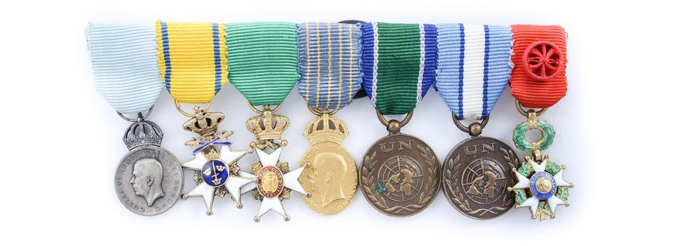 Även överste Waern mottog flera utmärkelser under sin karriär. Bilden visar Waerns miniatyrmedaljer, från vänster Gustav VI Adolfs minnesmedalj i silver med anledning av 85-årsdagen 1967; Svärdsorden; Vasaorden; Hemvärnets kungliga förtjänstmedalj i guld (stämplad 1970); FN-medalj för insatserna i Kongo respektive Cypern samt Franska Hederslegionen. Foto: Probus auktioner, Stockholm.