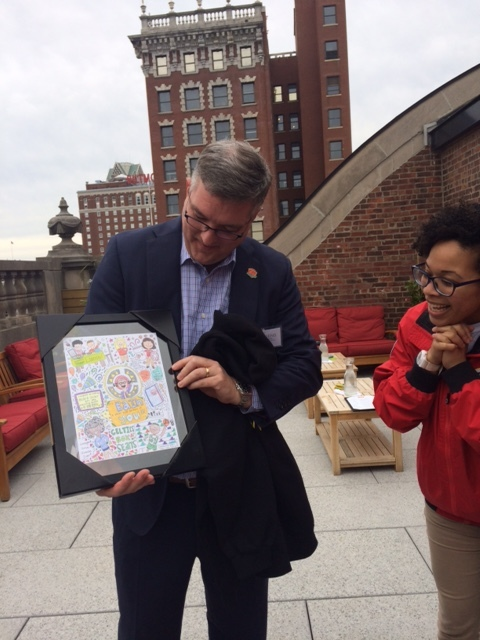 Andy Viens receives a thank you gift, a drawing by AmeriCorps Member Theda Tann, as AmeriCorps member Wilmaris Soto looks on