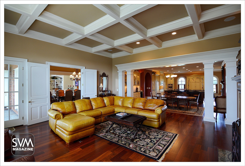 Inviting family room with beautiful coffered ceilings, granite fireplace, Brazilian cherry hardwood floors with view of formal dining room opens into casual dining area and the expansive kitchen.