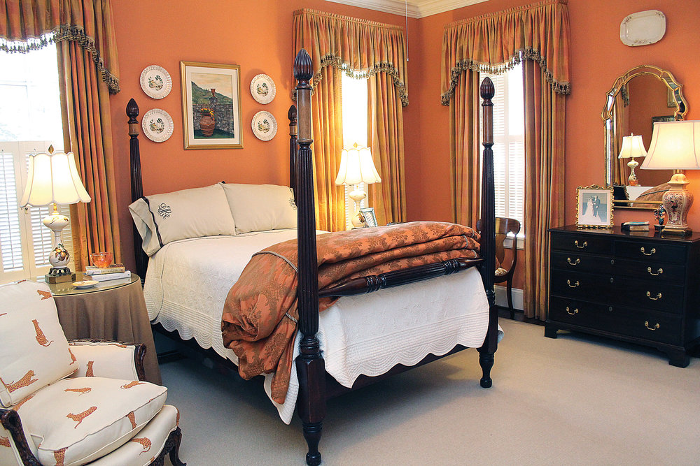 The master bedroom's terracotta walls create a sense of warmth and safety within the home. The antique mahogany four poster bed was purchased from an estate sale by the Helms. It was handcrafted from fine Honduran mahogany. The silk drapes were again custom made for the Helms by Frank Marlin.  The antiques around the room bring in a sense of timeless elegance.