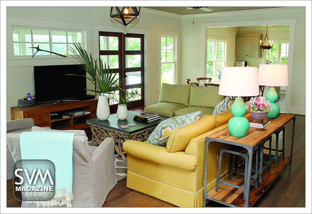 The family room is the heart of the home, and this living room reflects the family's vibrant personalities. The wooden floors throughout the home were found under the carpeting of the original house, and have been restored by Bone Flooring. The light fixture from The Big Chandelier gives off just enough brightness, without overpowering natural light from the huge windows. The coffee table from Currey & Co. has been the make-shift table for many dinners in front of the TV.