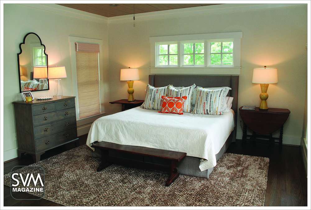 The remodeled master features a beautiful, wooden stained ceiling and huge windows for added natural light. The warm taupe rug from Flooring and More adds comfort, while the textured blinds by Berendt Company Shutters let in the desired amount of light on sunny mornings. The throw pillows from Romo Fabrics bring color to the room.