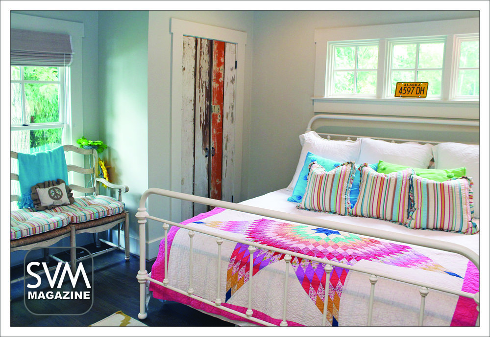 The guest bedroom features a reclaimed wood closet door by Tim Gregory and white furniture. The bright comforter and extra bench seating makes this room a guest favorite.