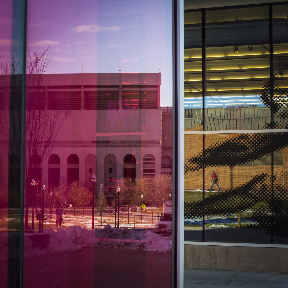 People are seen in reflective windows of the School of Physical Activity and Educational Services walking up and down West 17th Avenue in front of the Ohio Stadium Football Field in Columbus, Ohio on Wednesday, Dec. 18, 2013. The Ohio State University campus is quiet, cold and desolate after finals ended last week on December 11th and will start back for the Spring 2014 semester on January 6th.