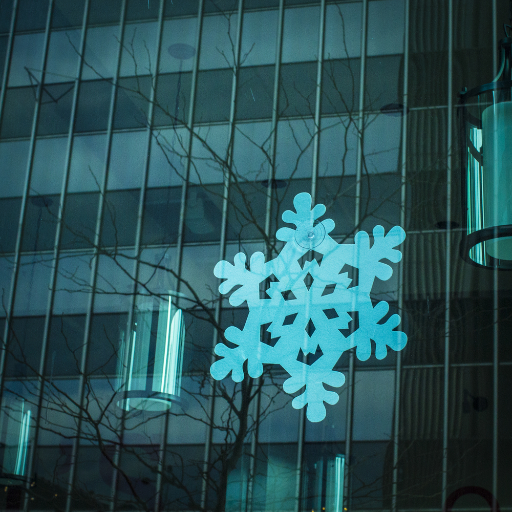 A snowflake cut out is seen in Lexi's on Third Restaurant as trees and the Key Bank Building are seen in the reflection in Columbus, Ohio on Saturday, Dec. 28, 2013. Downtown Columbus is relatively empty as many residences are at home enjoying time with their family and friends.