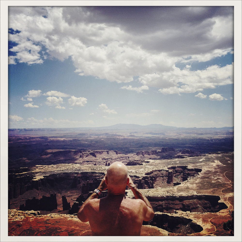 A shirtless man takes photos at the Grand View Point overlook on the Island in The Sky side of Canyonlands National Park in Utah.