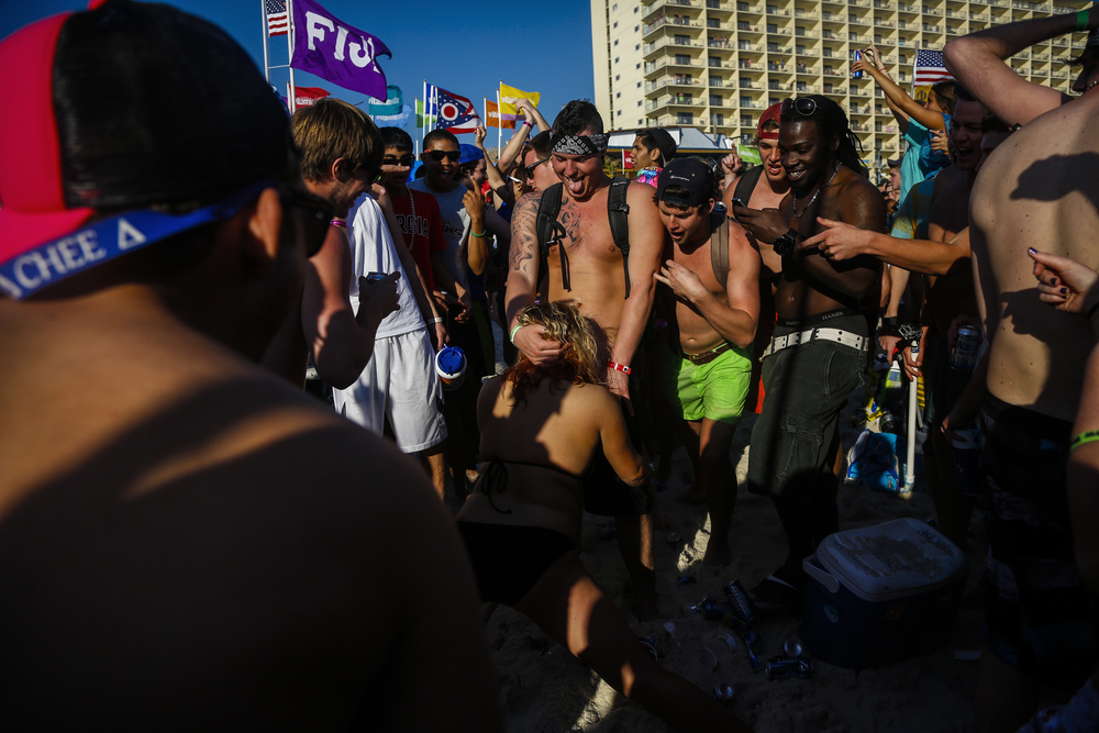 Spring breakers crowd around and cheer as a man receives oral sex from a female as students from around the country congregate to party and have a good time in Panama City Beach, Florida.