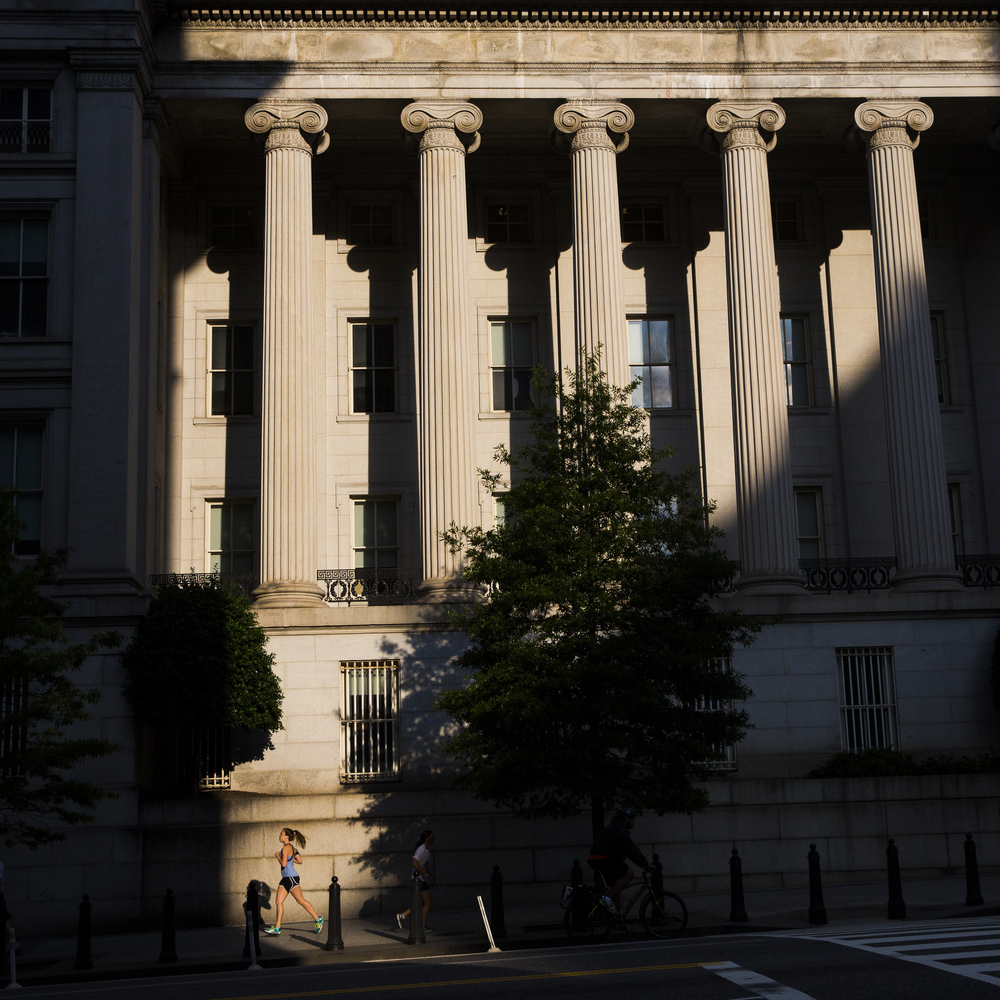 A runner jogs south on 15th Street North West by the U.S. Department of The Treasury on the morning of Tuesday June 3, 2014. The Treasury Building in Washington, D.C. is a National Historic Landmark building and is the headquarters of the United States Department of the Treasury.