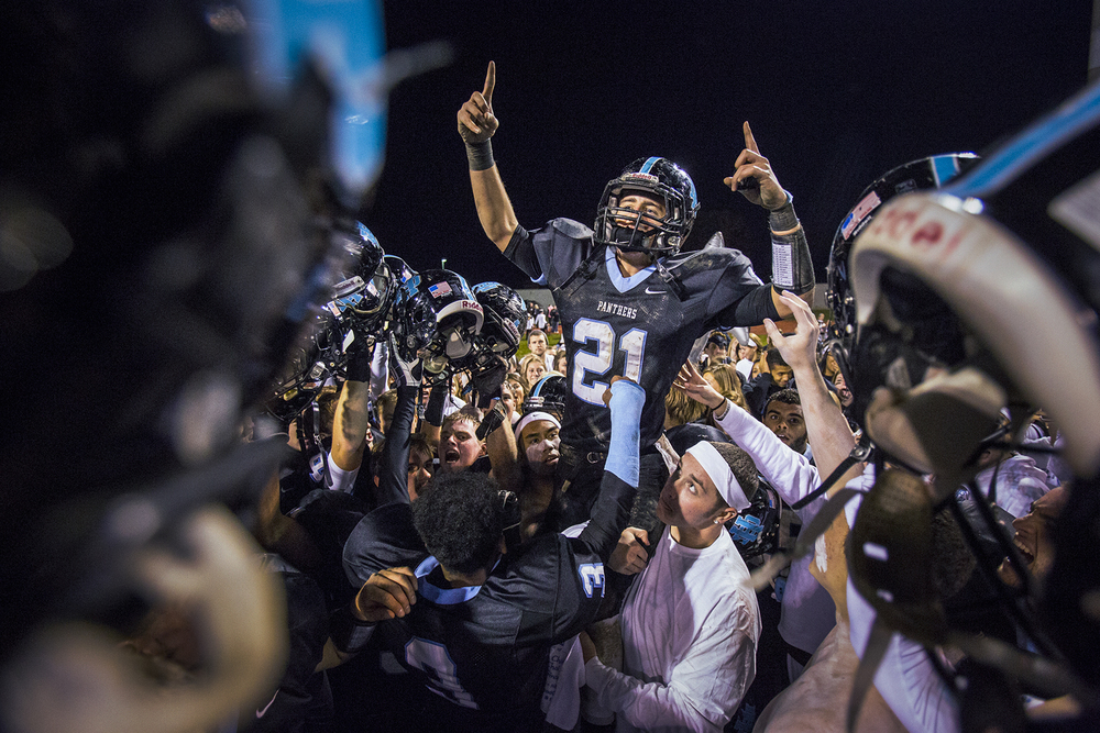 Hilliard Darby senior running back Hunter McSweeney is hoisted into the air as he celebrates with teammates and fans after a football game at Hilliard Darby High School in Columbus, Ohio on Thursday, Nov. 01, 2013.