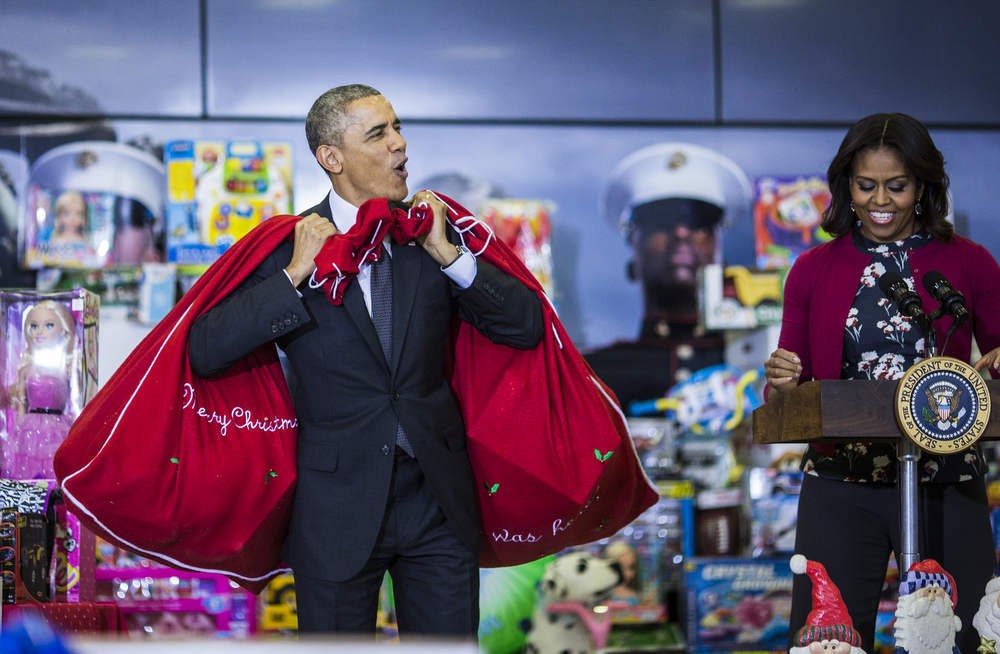 President Barack Obama and first lady Michelle Obama speak as they deliver toys and gifts donated by Executive Office of the President staff to the Marine Corpsí Toys for Tots Campaign at Joint Base Anacostia-Bolling in Washington, DC on Wednesday December 10, 2014.
