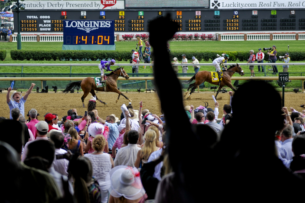 Fans erupt during a race leading up to 138th Kentucky Oaks horse race at Churchill Downs in Louisville, Ky., on Friday, May 5, 2012. Fans from all sources wagered $39.9 million on the day of the Oaks, a 6.5-percent increase from the previous year and $226.9 million was wagered from all sources on the Kentucky Derby weekend.