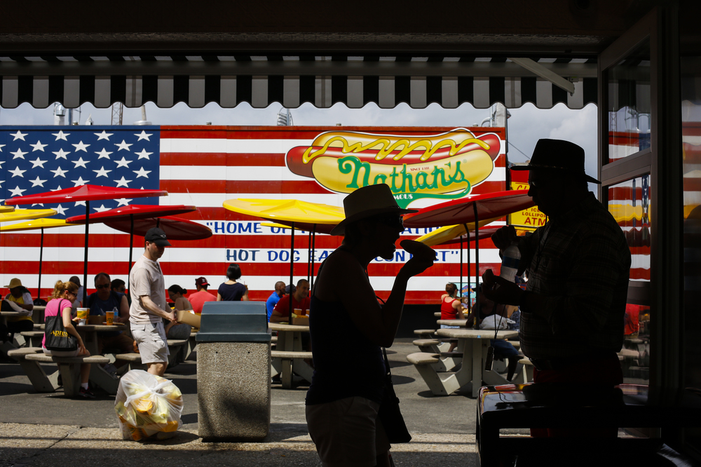 Patrons enjoy the fourth of July holiday with a hot dog before the 97th annual Nathan's Famous Fourth of July International Hot Dog Eating Contest at Coney Island in Brooklyn, N.Y. on Thursday, July 4, 2013.