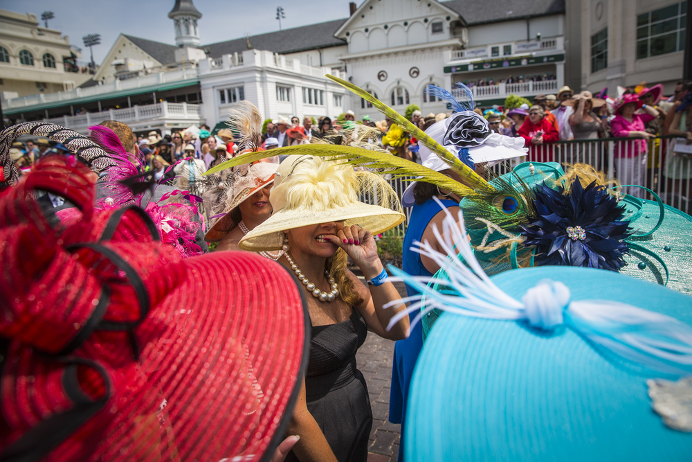 Patrons with their derby hats watch as horses circle the paddock on the day of the 140th Kentucky Derby at Churchill Downs in Louisville, Ky. on Saturday May 03, 2014.