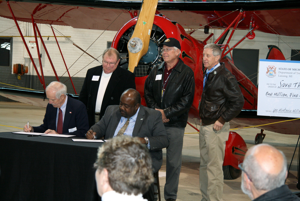 Ray Hunter of the Yankee Air Museum and Elliot Laws of RACER Trust sign documents making the Museum the new owner of a preserved portion of the historic Willow Run Bomber Plant.