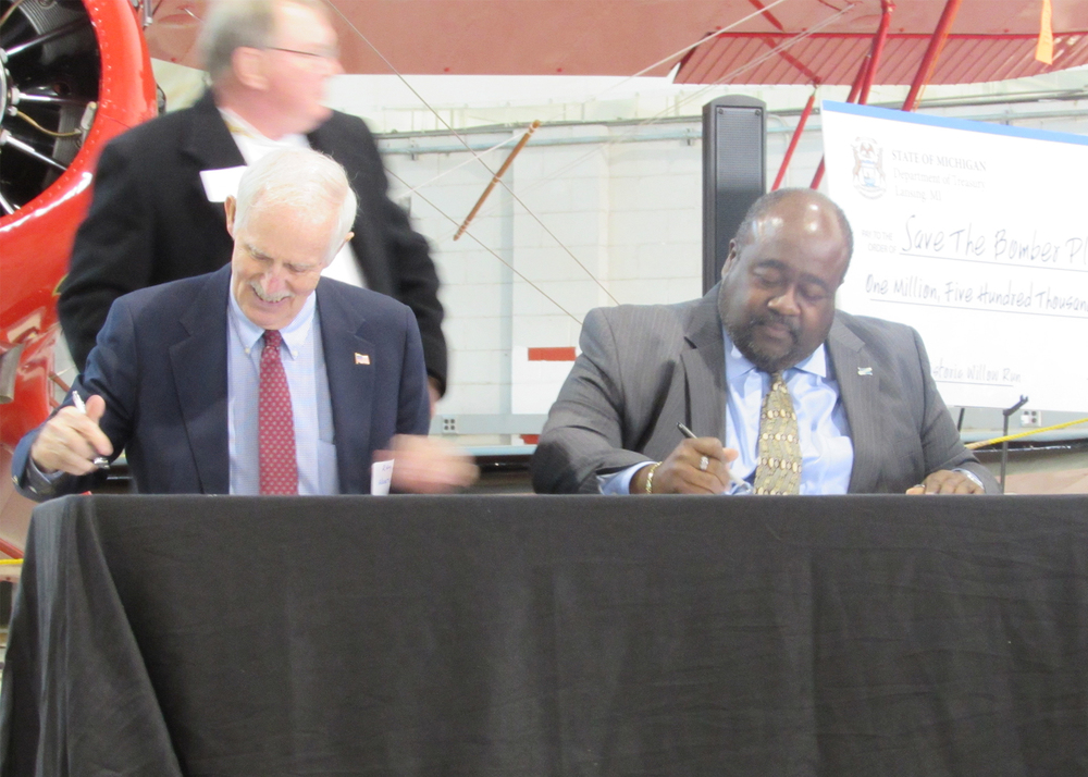 Ray Hunter of the Yankee Air Museum and Elliott Laws of RACER Trust sign documents transferring ownership of 144,000 sq. ft. of the former WIllow Run Bomber Plant to the Yankee Air Museum.