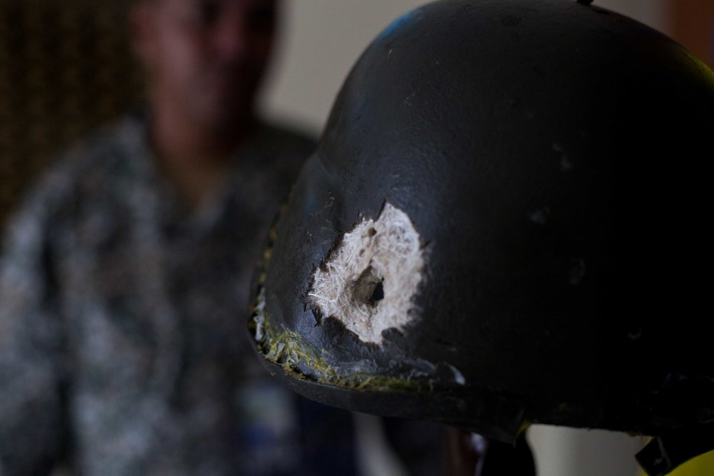 Soldier holds a Marine helmet with a bullet hole.  Marines Museum at the Marines Training Base (Coveñas, 2016).