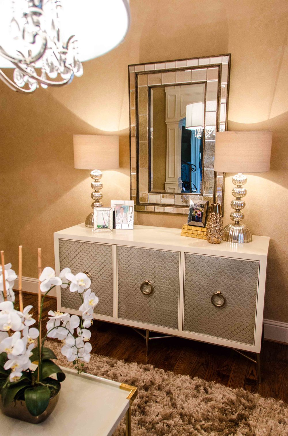 Transitional silver leaf and cream console with a mirror above