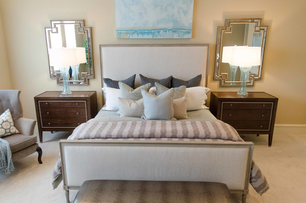 Gray upholstered headboard and dark wood night stands, in a transitional master bedroom