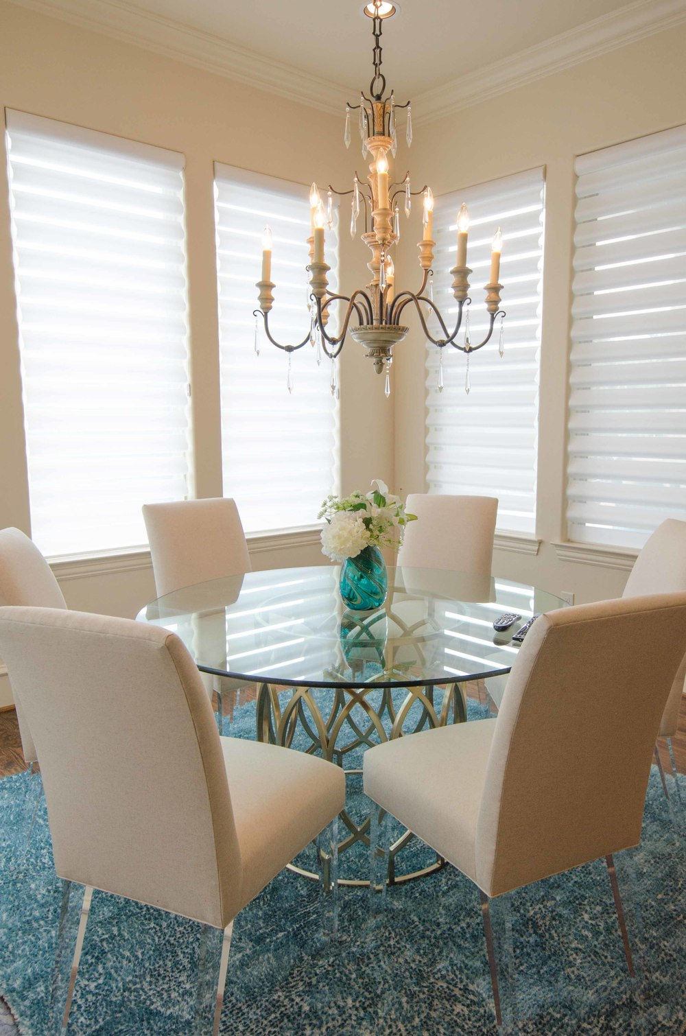 Transitional dining room with gold base and glass top table and chairs with lucite legs. Turquoise shag rug.