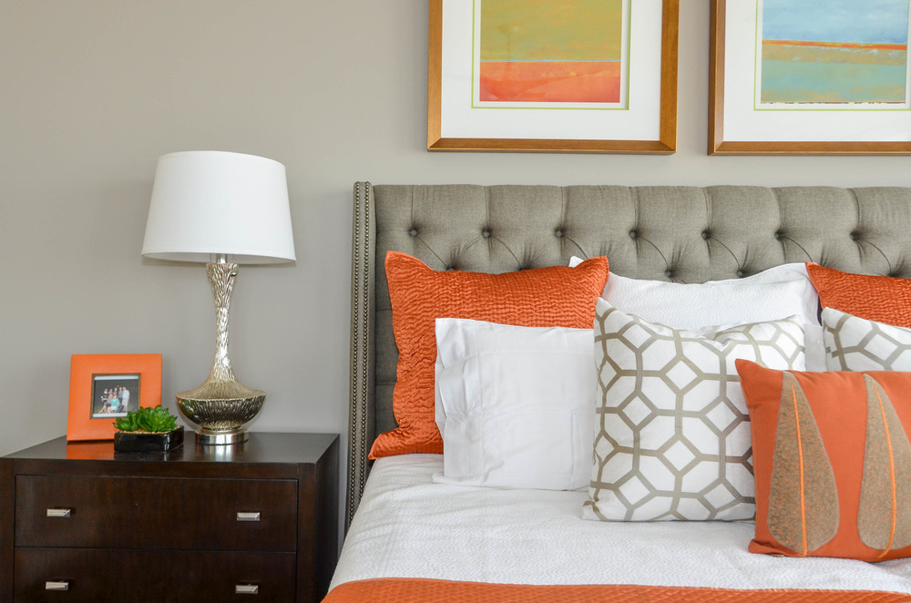 Modern grey tufted headboard with art above and orange accents
